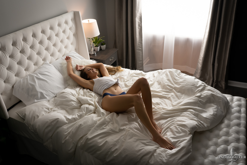 casual boudoir of woman laying on bed smiling