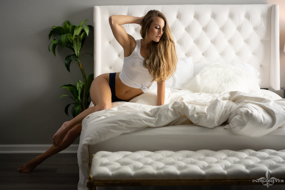boudoir photo of woman sitting on edge of bed
