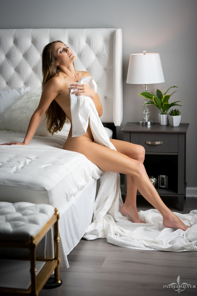 implied nude photo of woman wrapped in sheets