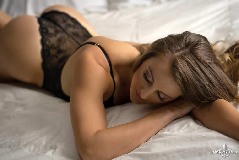 boudoir photo of woman laying on bed with black bodysuit